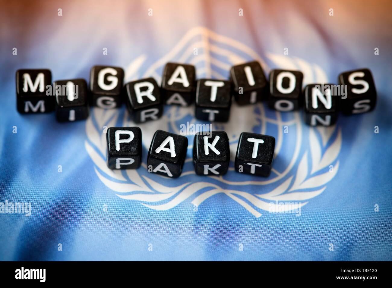 Die Woerter MIGRATIONS PAKT auf einer UN-Flagge, aus Buchstabenwuerfeln gebildet | Lettering MIGRATIONS PAKT (UN migration pact) on top of the UN flag - Stock Image
