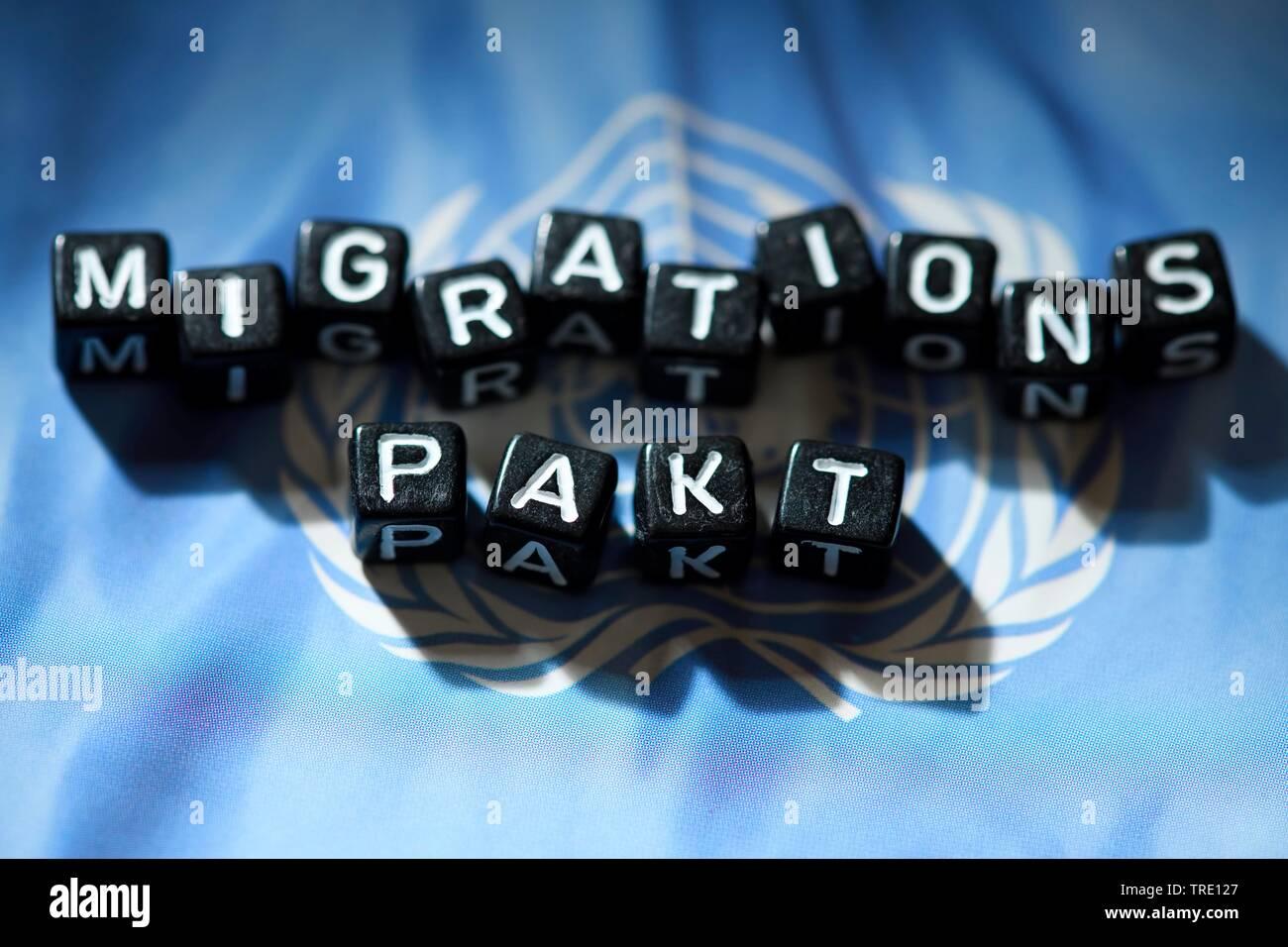 Die Woerter MIGRATIONS PAKT auf einer UN-Flagge, aus Buchstabenwuerfeln gebildet   Lettering MIGRATIONS PAKT (UN migration pact) on top of the UN flag - Stock Image
