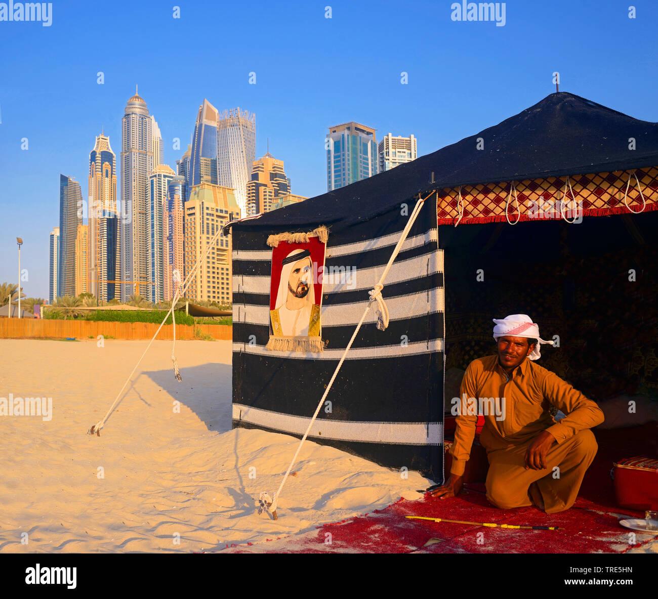 Beduine vor seinem Zelt, Wolkenkratzer von Dubai im Hintergrund, Vereinigte Arabische Emirate, Dubai | bedouin man and his camp in front of skyscraper - Stock Image