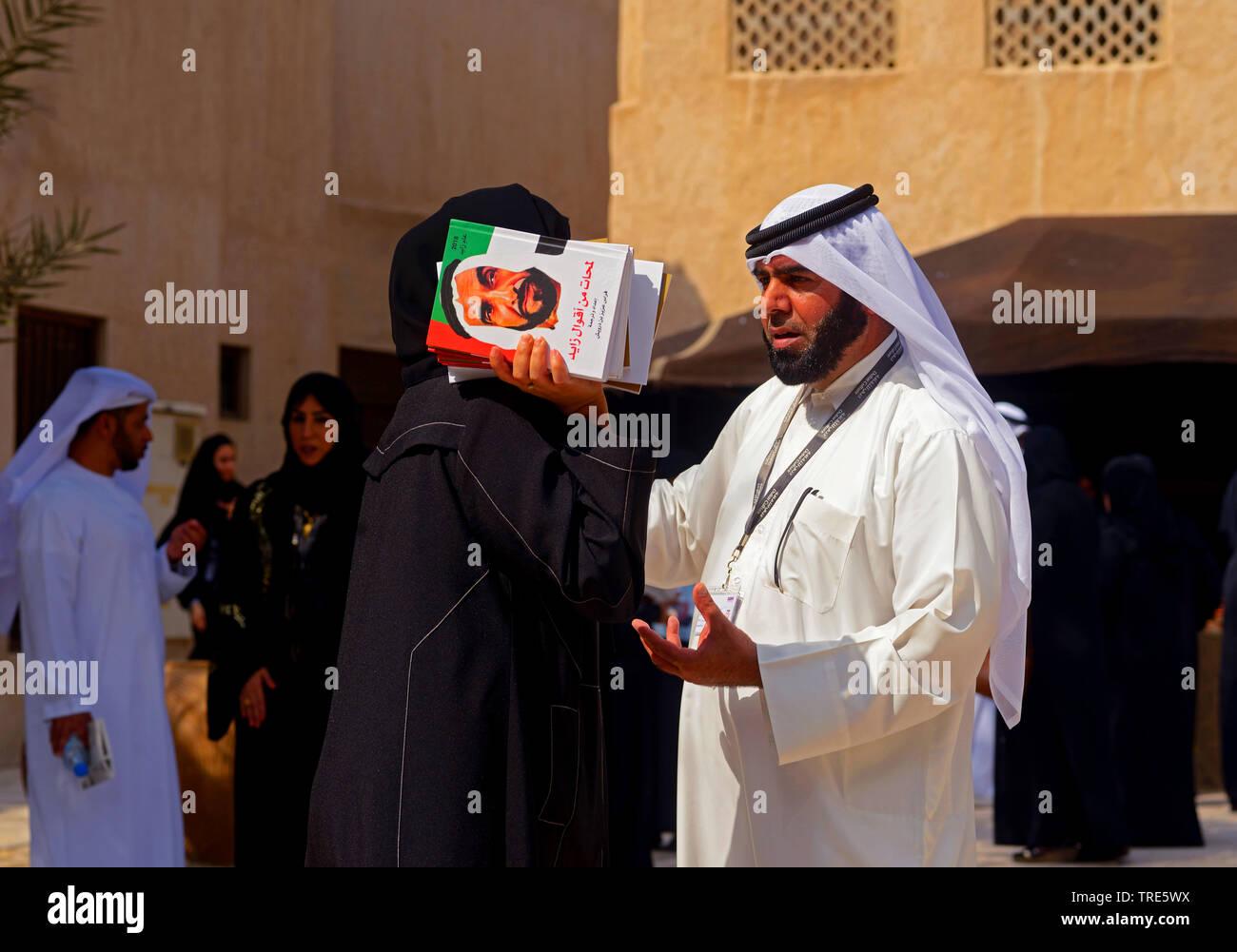 Frau mit Buechern von Scheich Zayid, dem ersten Praesidenten der Vereinigten Arabischen Emirate, unterhaelt sich, Vereinigte Arabische Emirate, Dubai - Stock Image
