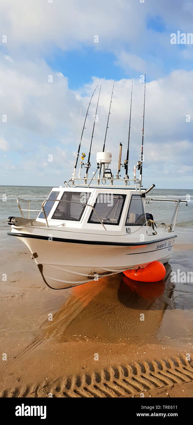 Boot mit vielen Angeln an Bord liegt am Strand an der Nordsee, Niederlande | boat with a lot of fishing rods on the beach of the North Sea, Netherland - Stock Image