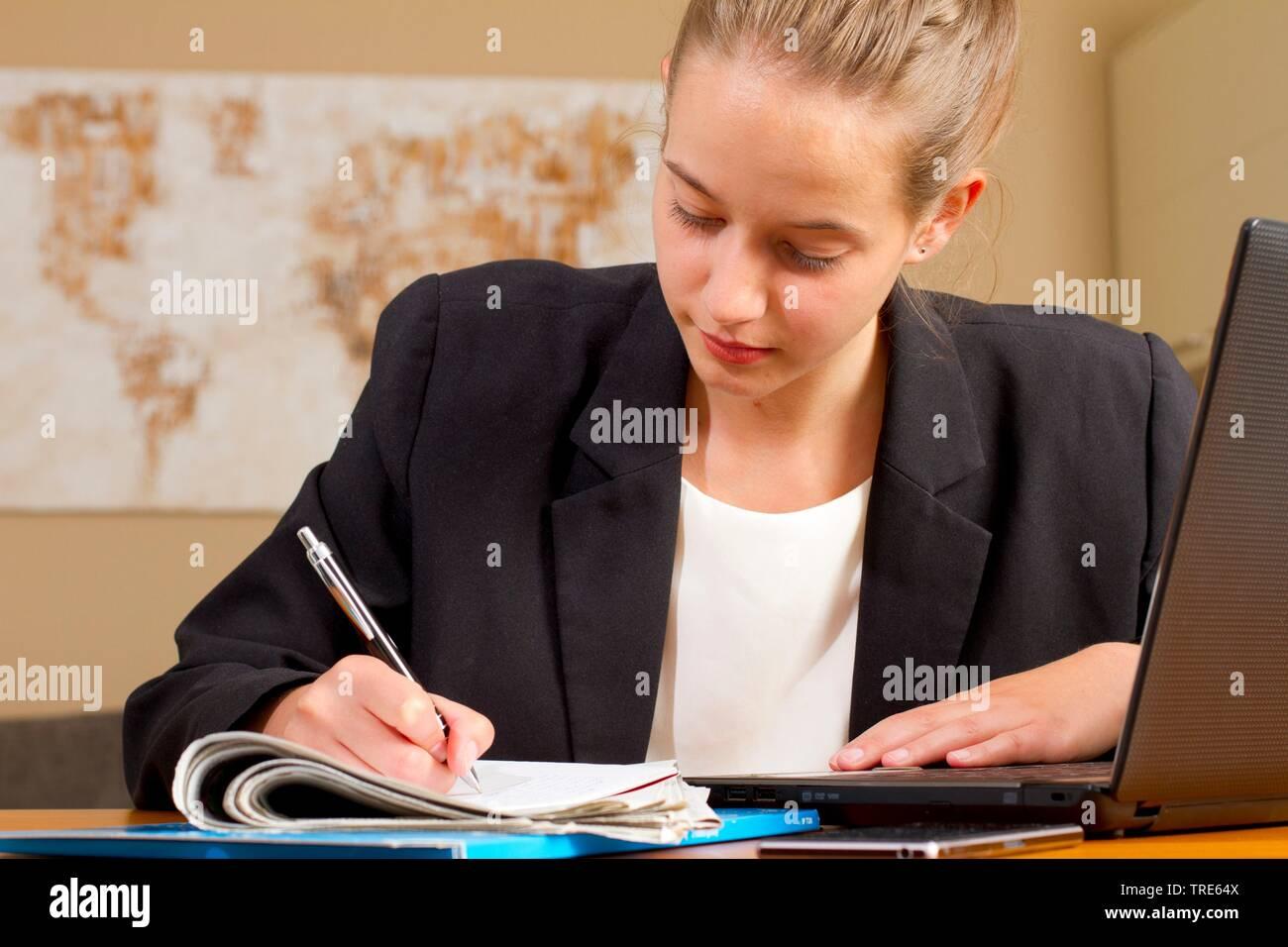 Portraet einer jungen Frau, am Schreibtisch arbeitend | Portrait of a young woman working at a desk | BLWS518265.jpg [ (c) blickwinkel/McPHOTO/A. Pulw - Stock Image