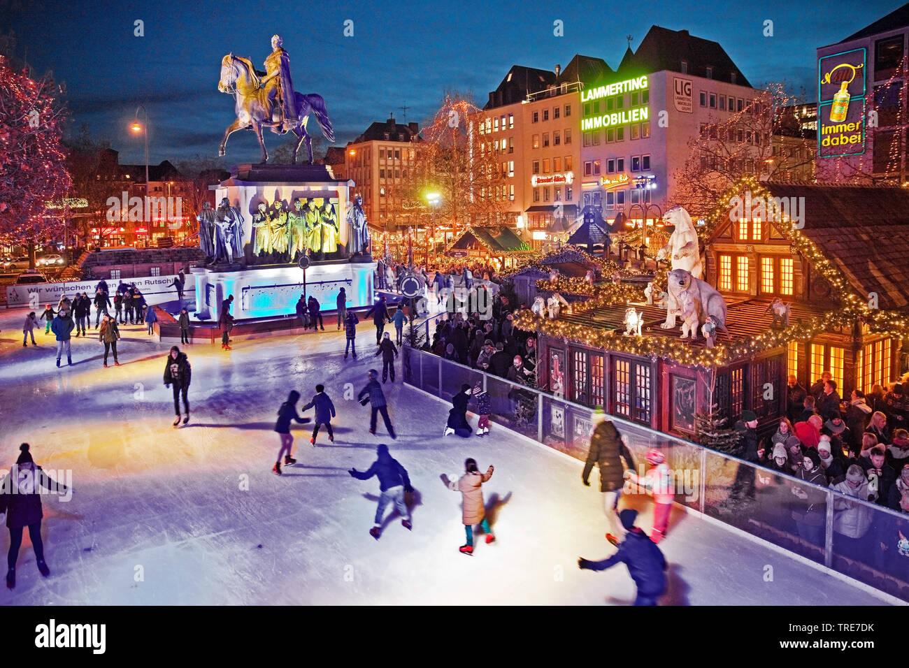 Menschen auf der illuminierten Eisbahn auf dem Heumarkt mit Reiterstandbild Friedrich Wilhelm III, Deutschland, Nordrhein-Westfalen, Koeln   ice skati - Stock Image