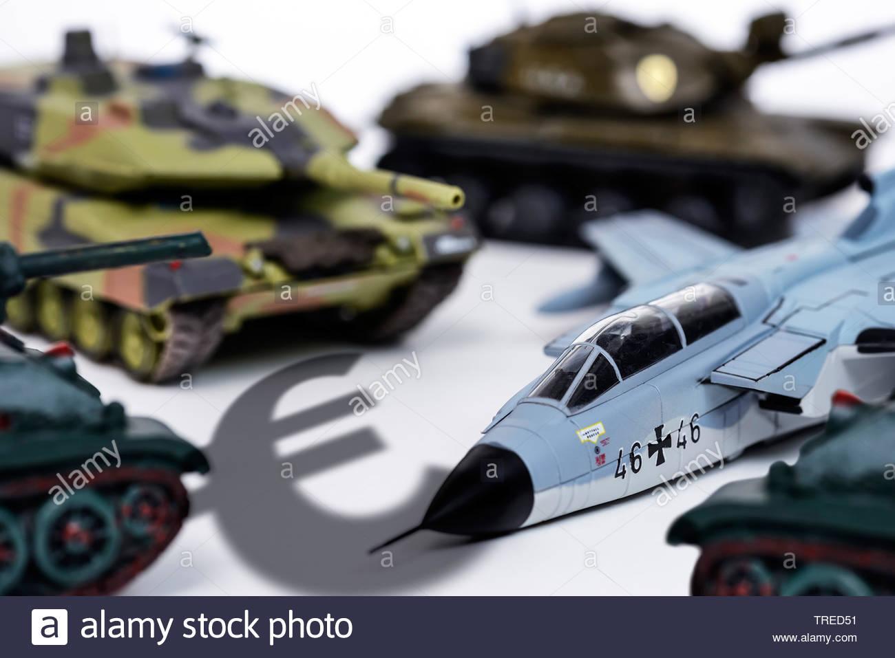 Militaerisches Spielzeug (Panzer und Flugzeuge) und ein Euro-Zeichen - Verteidigungsausgaben   Military toys (tanks and aircrafts) and an Euro sign - - Stock Image