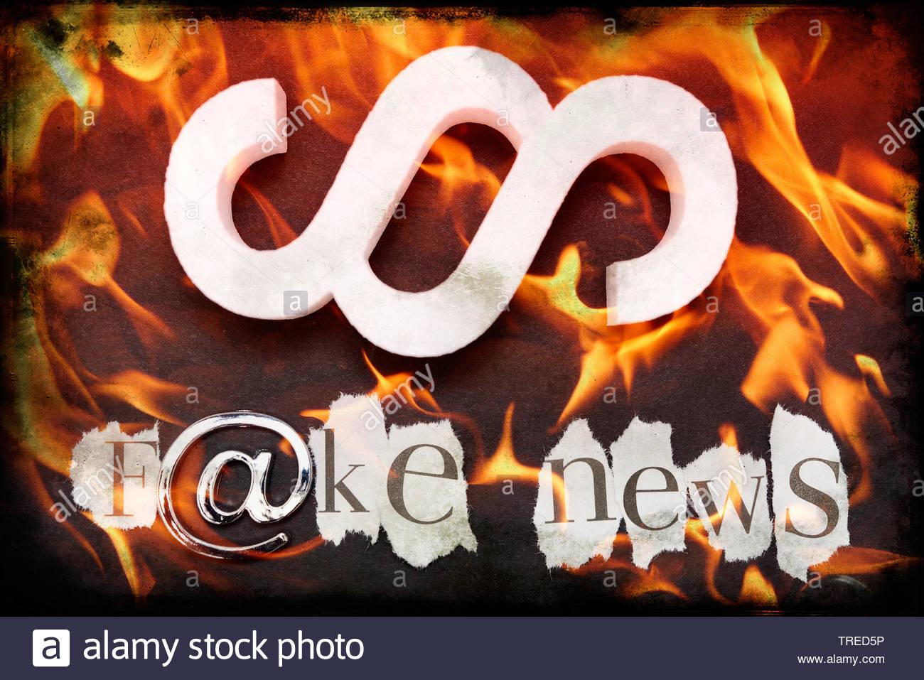 Aufschrift F@KE NEWS (Falschnachrichten) und ein Paragraphenzeichen vor rotem Hintergrund mit Flammen | Lettering F@KE NEWS and a law paragraph mark - Stock Image