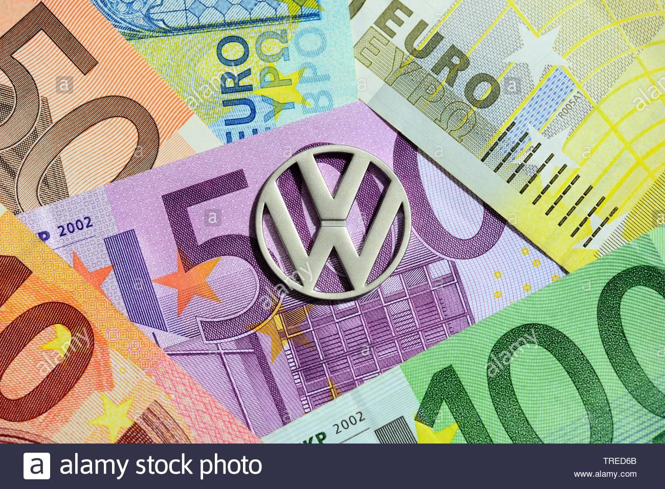 Volkswagen Firmenlogo mit Euroscheinen im Hintergrund - Strafzahlung Dieselaffaere | Volkswagen logo against Euro bills - penalty for diesel emissions - Stock Image