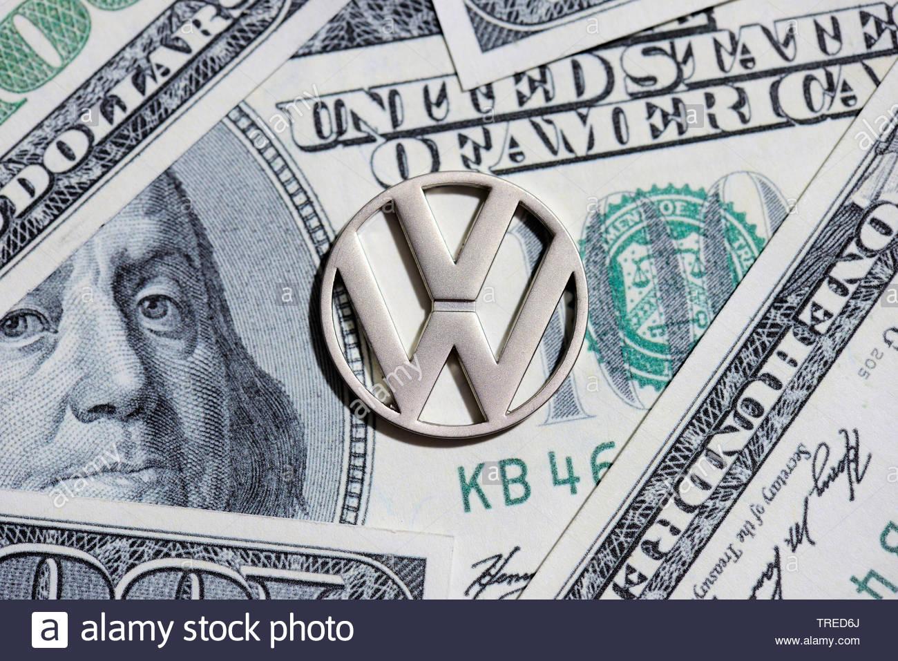 Volkswagen Firmenlogo mit Dollarnoten im Hintergrund - Strafzahlung Dieselaffaere | Volkswagen logo against Dollar bills - penalty for diesel emission - Stock Image