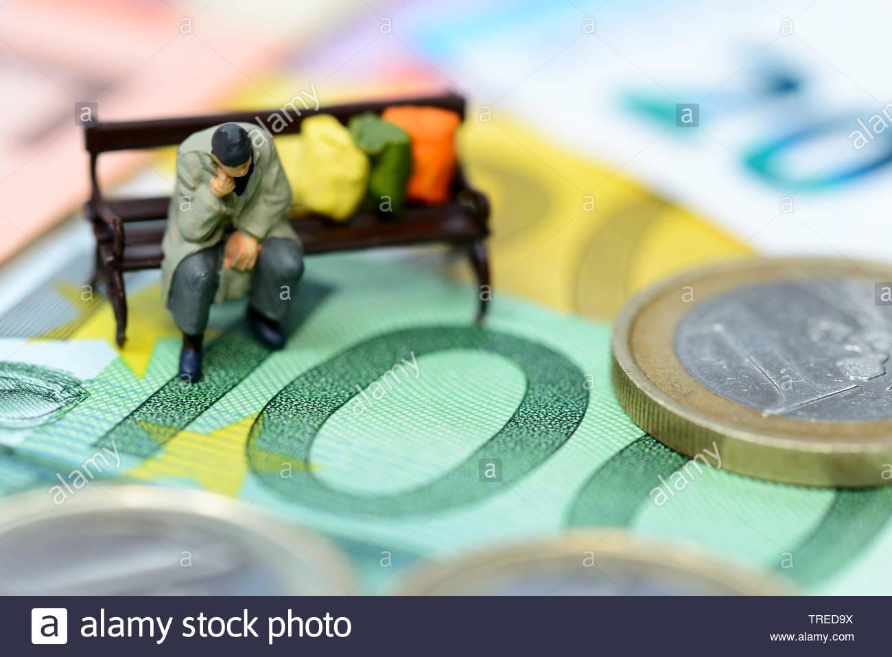 Spielfigur auf einer Parkbank sitzend mit Euroscheinen im Hintergrund - Altersarmut | Toy figure sitting on a park bench on tp of Euro bills - elderly - Stock Image