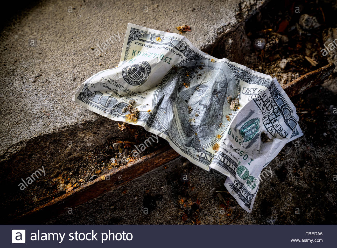Crumpled 100 Dollar note lying on the ground - increasing national deficit in the US Stock Photo