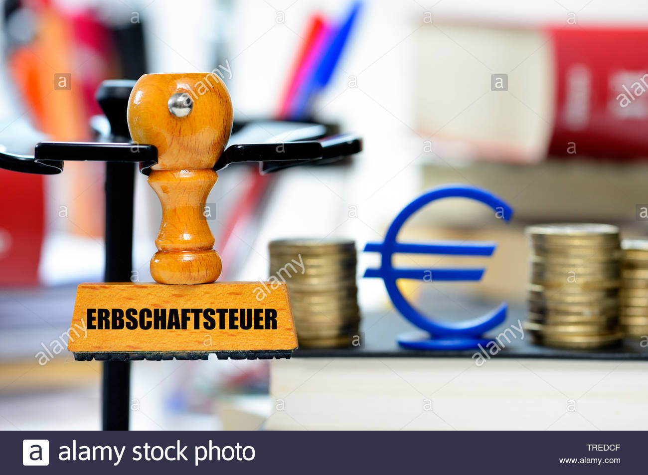 Stempel mit Aufschrift ERBSCHAFTSTEUER vor einem Eurozeichen und Euro-Muenzen, Bundesrepublik Deutschland | Stamp lettering ERBSCHAFTSTEUER (inheritan - Stock Image