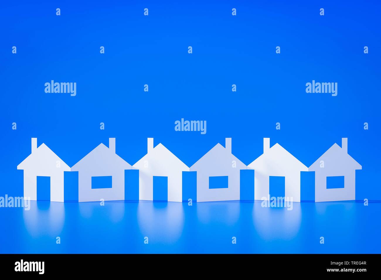 3D-Computergrafik, Scherenschnitt von weissen Haeusern vor blauem Hintergrund | 3D computer graphic, paper cutout row of white houses against blue bac - Stock Image