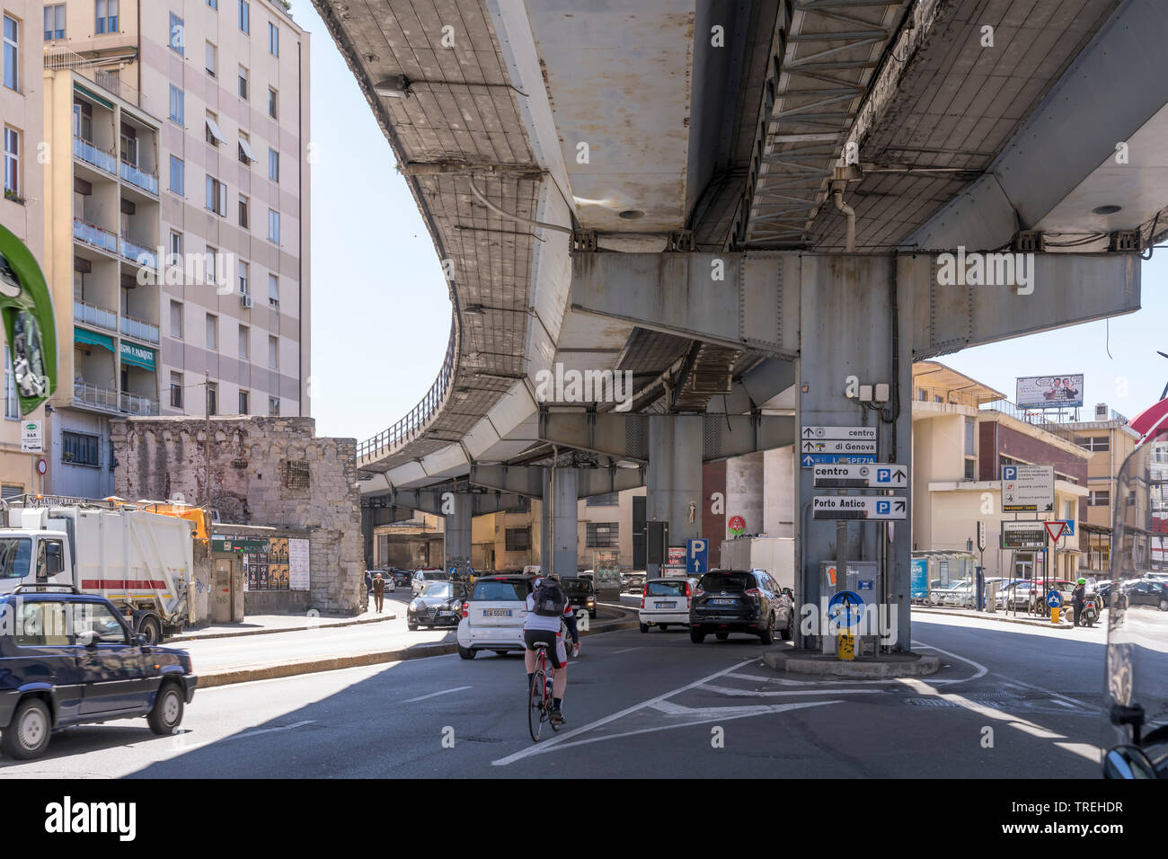 GENOVA, ITALY - MAY 16: traffic flows under 60's skyway passing by urban renewal area of sea town historical harbor. Shot on a sunny spring day on may - Stock Image