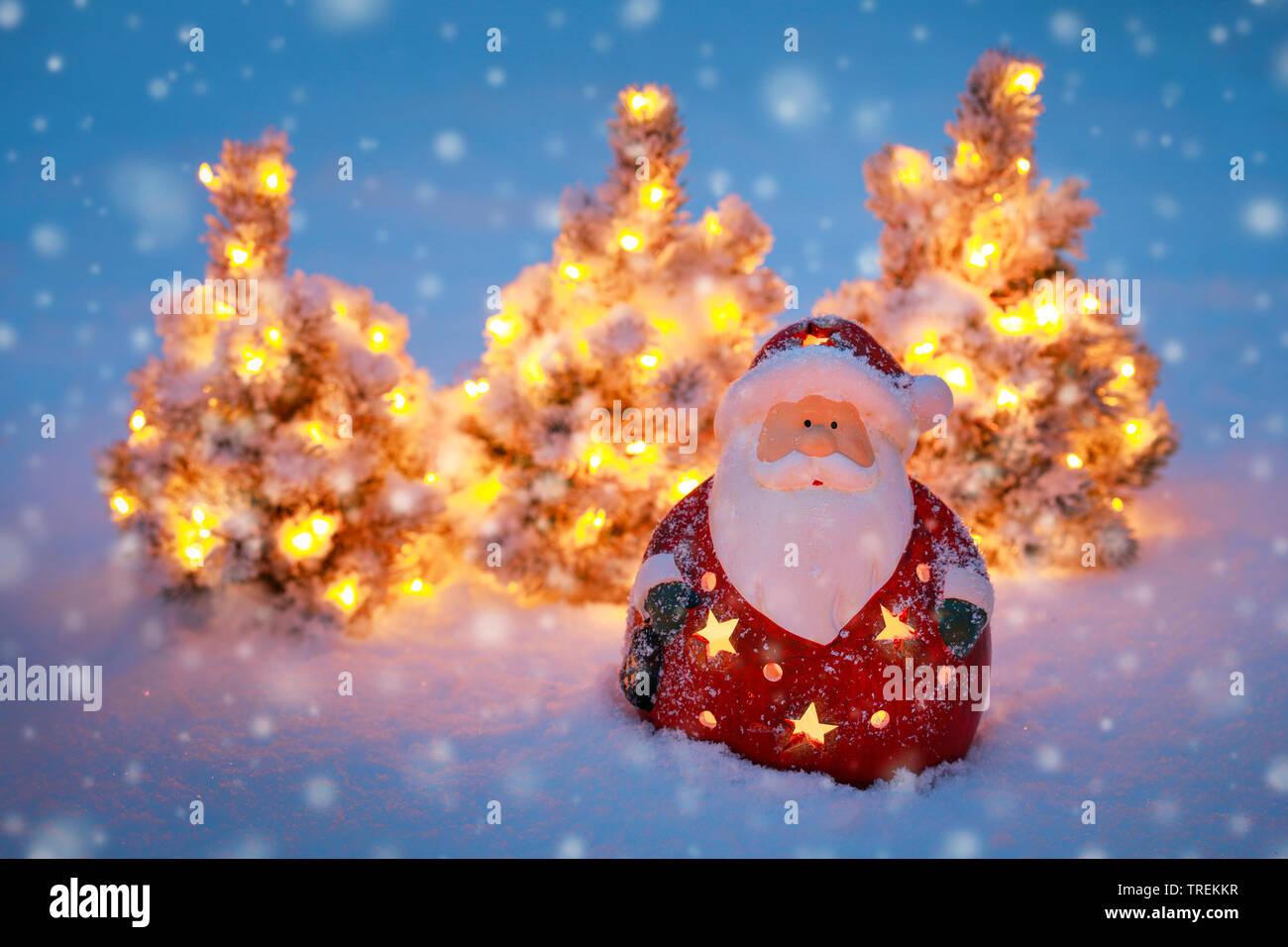 Weihnachtsmannfigur und kleine beleuchtete Weihnachtsbaeume im Schnee | Santa Claus and small illuminated Christmas trees in snow | BLWS528479.jpg [ ( - Stock Image