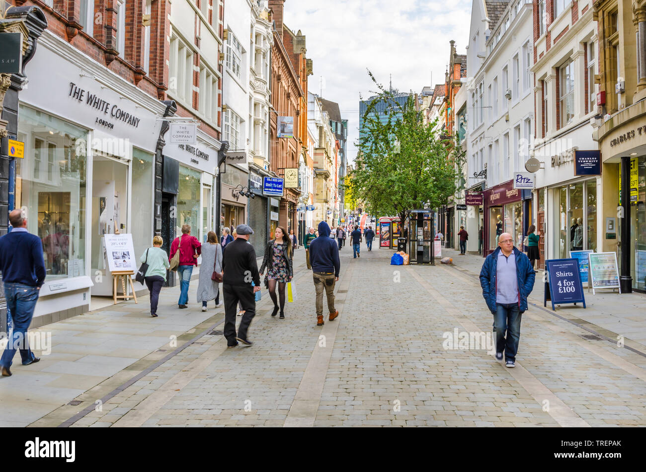 Shoppers and tourists strolling around King Street in central Manchester, UK, on a warm autumn day - Stock Image