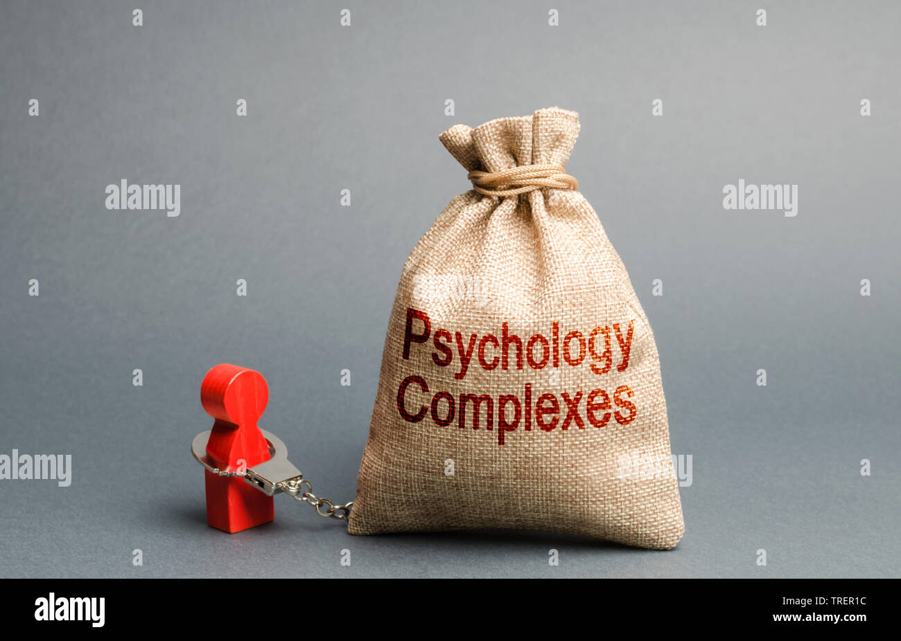 A person is handcuffed with a bag labeled psychological complexes. Feeling of inferiority and low self-esteem, low social skills, sociopathy and lack - Stock Image