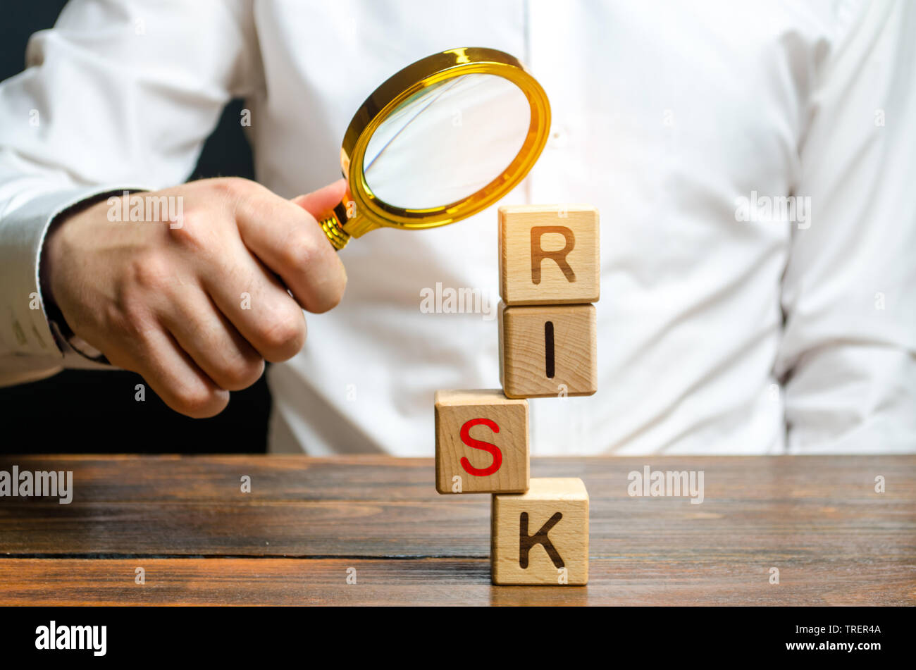 A man explores a tower of cubes with the word Risk. Search and correction of errors and failures. Risk management, cost assessment, and business and i - Stock Image