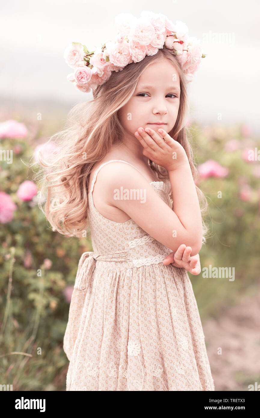 90ab900af9 Smiling baby girl 3-4 year old wearing stylish dress and wreath with roses  outdoors. Looking at camera. Childhood.