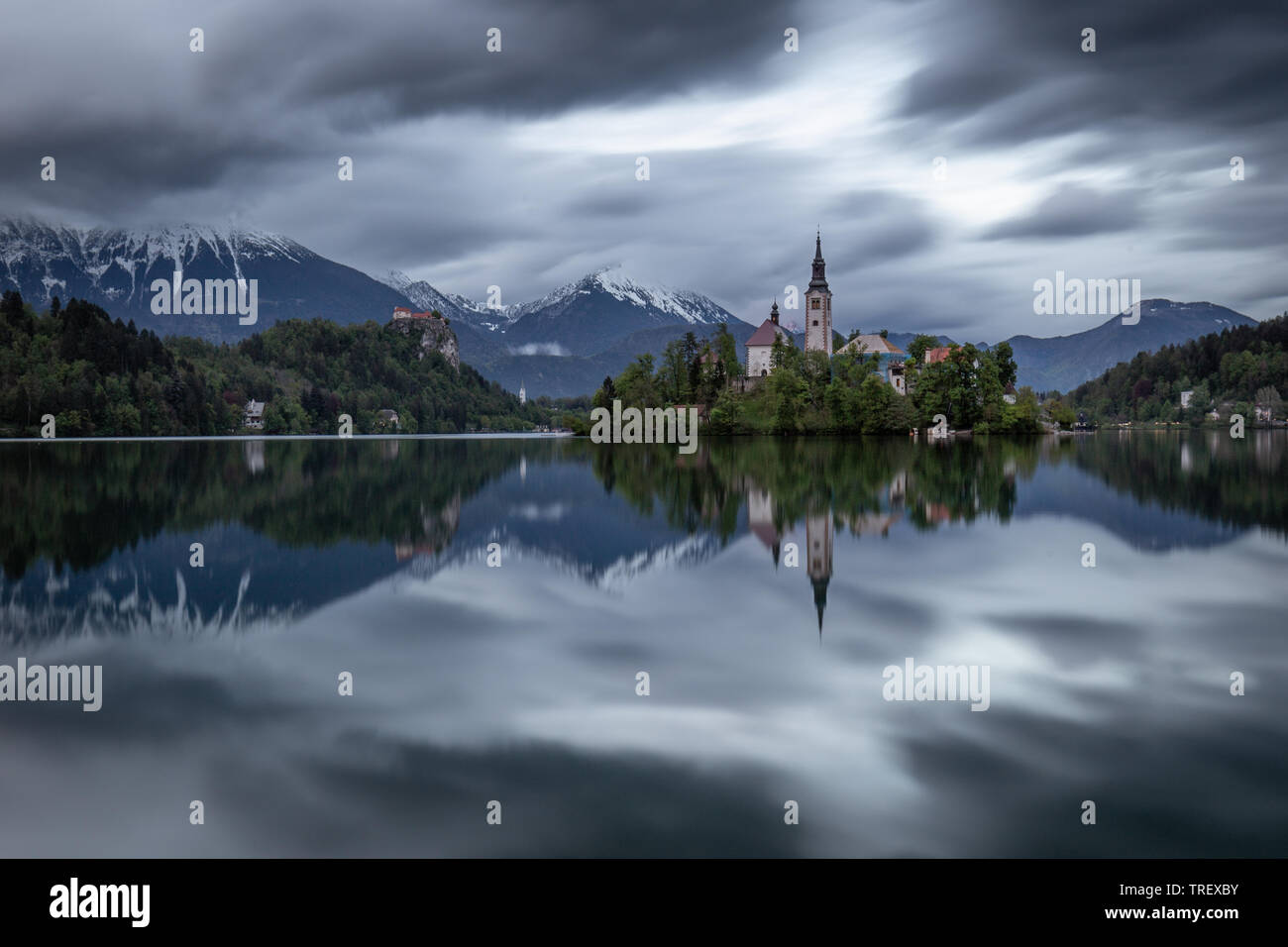 Dramatic sky with moving clouds over Assumtion of Mary church on island at Lake Bled, Slovenia. Long time exposure view of church and castle Bled refl Stock Photo