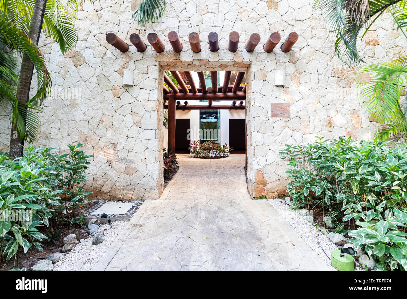 The entrance to one of the hotel buildings, surrounded by plants, at the Valentin Imperial Maya all inclusive resort. - Stock Image