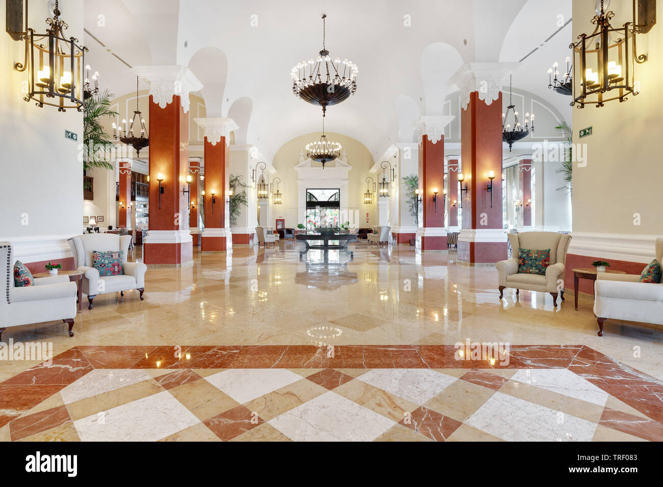 A beautiful lobby inside of the Valentin Imperial Maya all inclusive resort with organized decorations, seating, and chandeliers. - Stock Image