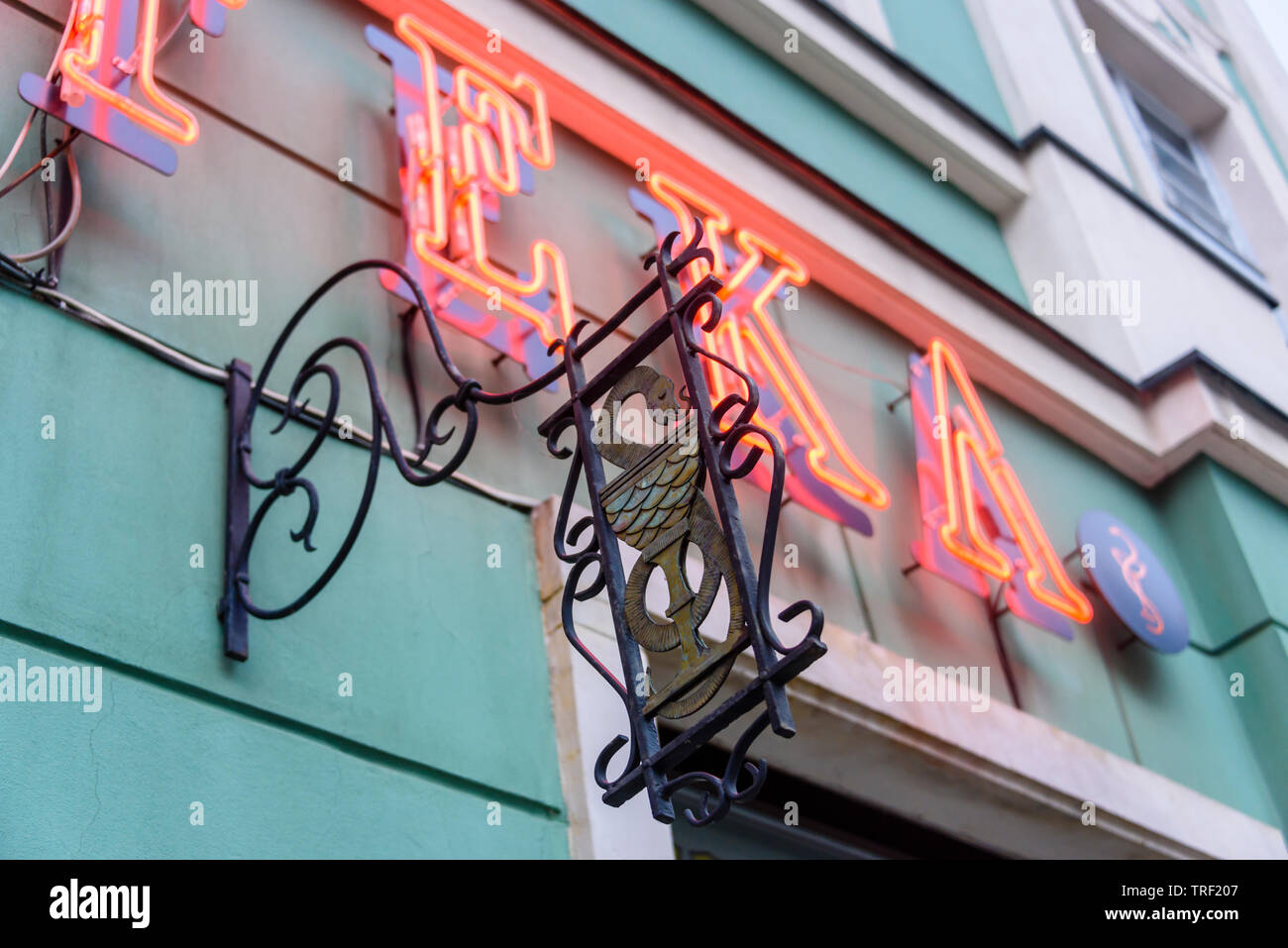 Neon sign saying 'Apteka' with a traditional snake symbol outside a pharmacy chemists shop, Wrocław, Wroclaw, Wroklaw, Poland - Stock Image