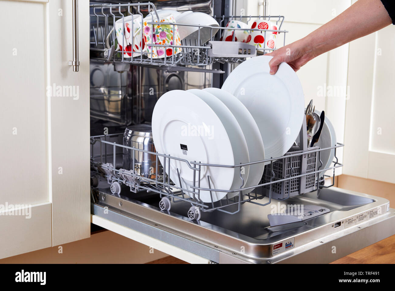 Woman unloading clean dishwasher - Stock Image