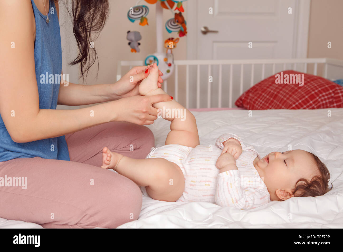 Portrait of cute adorable mixed race Asian mother with newborn baby doing massage and physical exercises. Early development and health care lifestyle Stock Photo