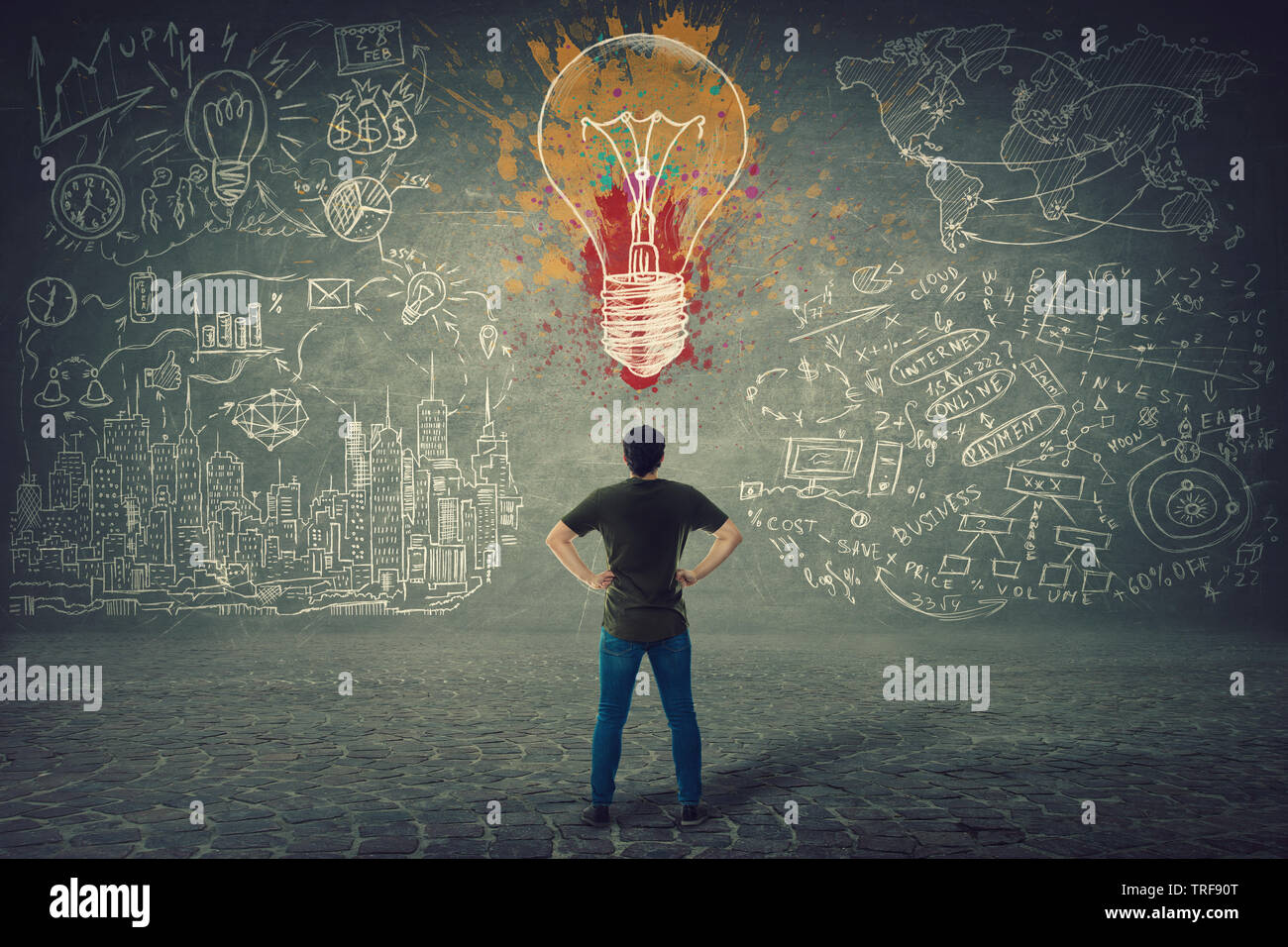 Rear view of confident young man, hands on hips, stands in front of a wall with drawn colorful light bulb and business sketches. Uniqueness of the ide Stock Photo