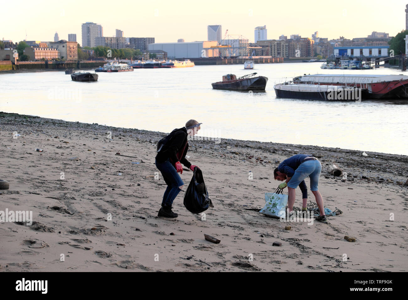 Two young people picking up rubbish and view of River Thames on the riverside waterfront at low tide in Rotherhithe South London SE16 UK  KATHY DEWITT - Stock Image