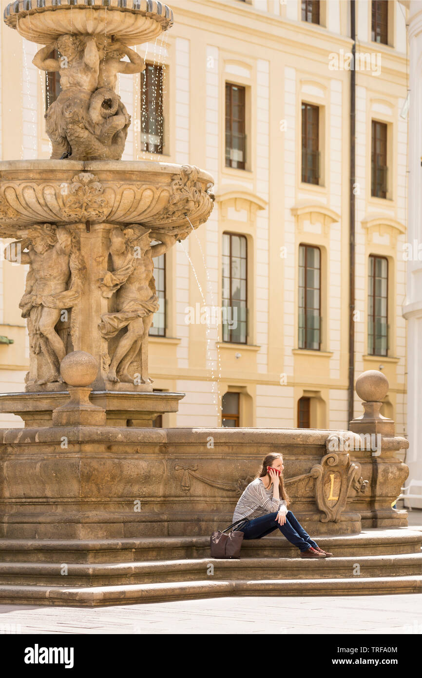 Happy, smiling young woman tourist solo traveler talking on mobile cell phone in European city, Prague, Czech Republic - Stock Image