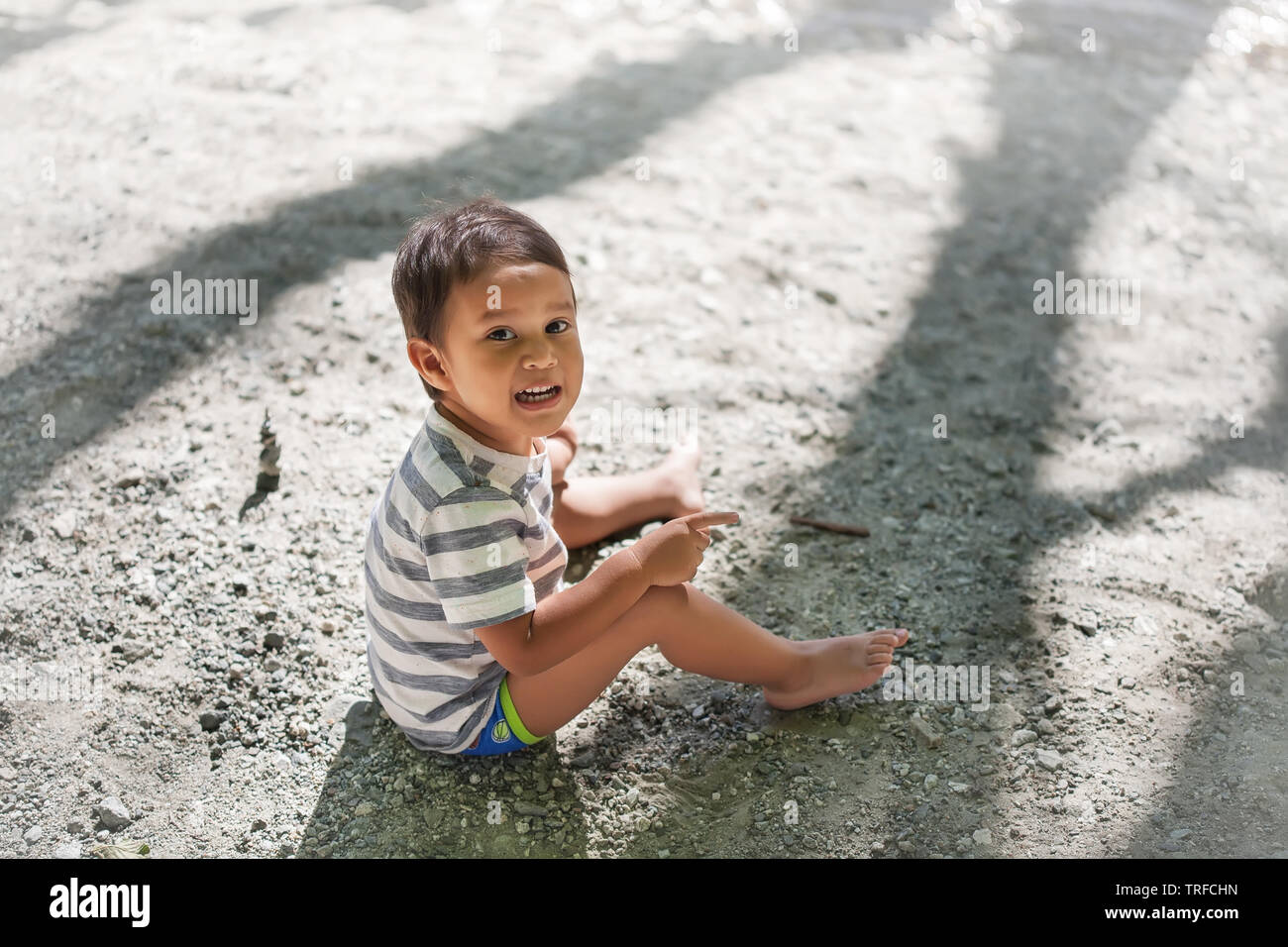 7034300231 Little boy wearing swimming shorts while sitting near the river shore as he  tries to talk
