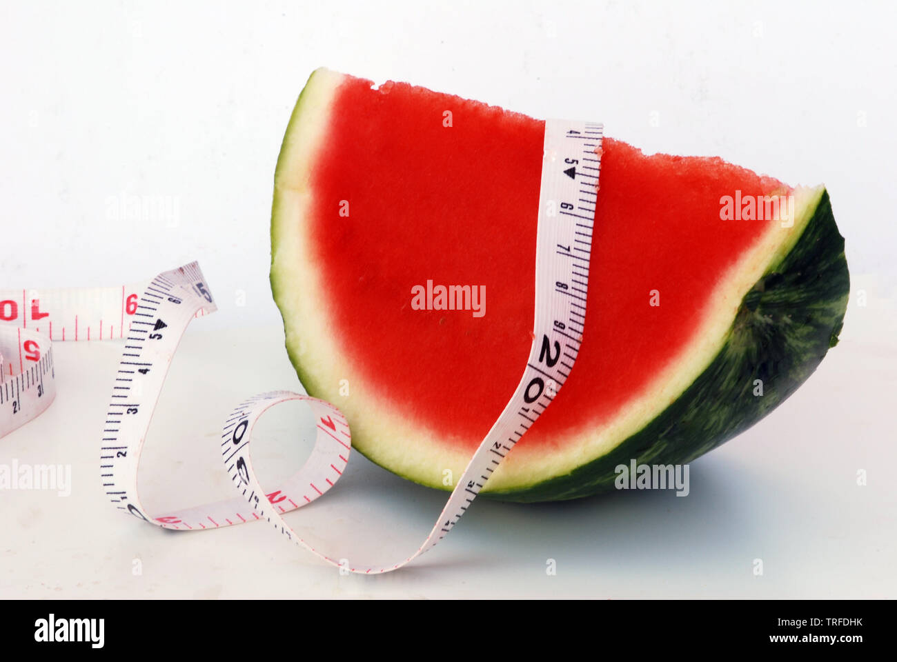 A piece of watermelon with measuring tape - Stock Image