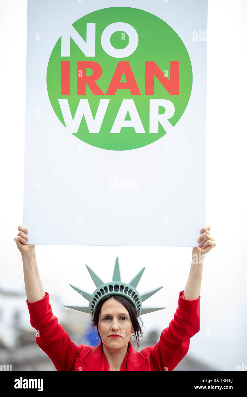 London, UK. 4th June 2019. Anti-war protester holds a large board with no to Iran war on Trafalgar Square on the day protesters holding a mass protest in central London on Trafalgar Square, Whitehall and Parliament Square against the President of the USA, Donald Trump, visiting the UK. Credit: Joe Kuis / Alamy - Stock Image