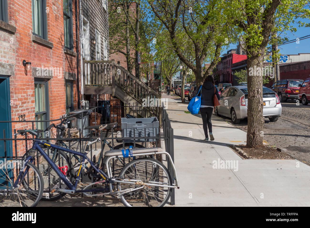 a woman walks down a sreet in brooklyn, ny - Stock Image