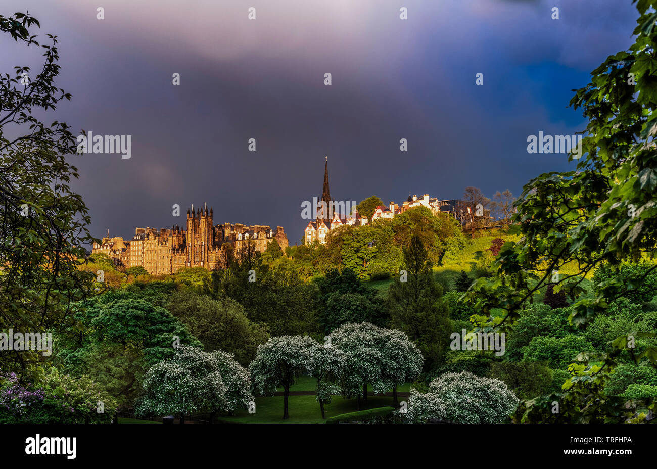 View of The Mound, St Giles Cathedran spire and Ramsay Gardens from Princes Street in dramatic low light, Edinburgh Stock Photo