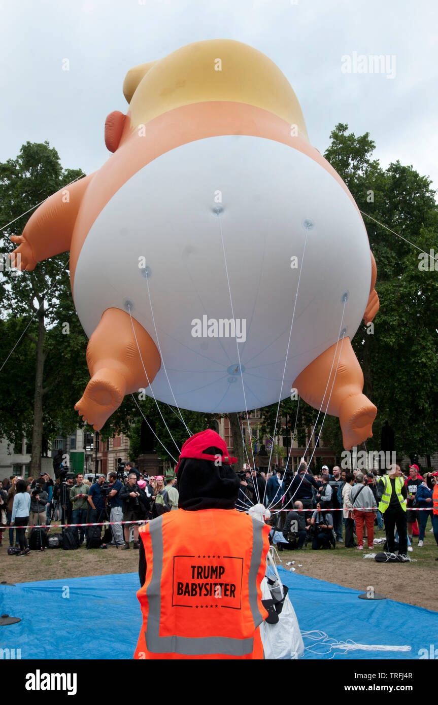 Protest against the state visit of President Trump in Parliament Square, London on June 4th 2019. Back view of Trump Baby blimp with an activist known - Stock Image