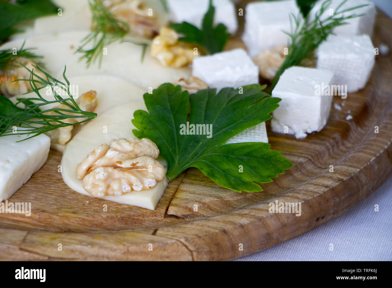 Extreme close-up of different types of cheeses, nuts, herbs and honey on a wooden board, the concept of a healthy snack, copyspace Stock Photo