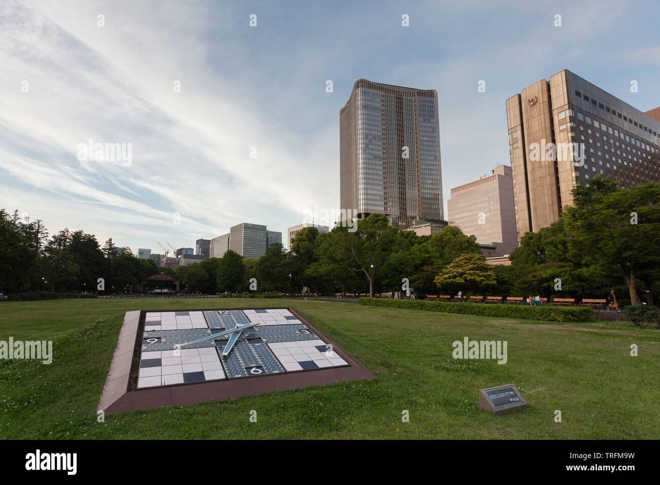 A solar-powered clock in Hibiya Park, With the towers  of Tokyo Midtown-Hibiya and The Imperial Hotel behind Hibiya, Tokyo, Japan. Monday June 3rd 201 - Stock Image