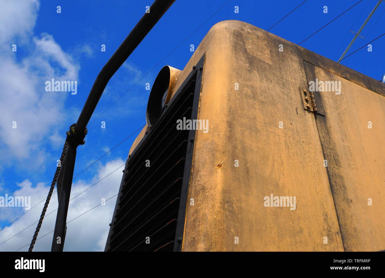 Abstract of a yellow small locomotive with blue sky in background - Stock Image