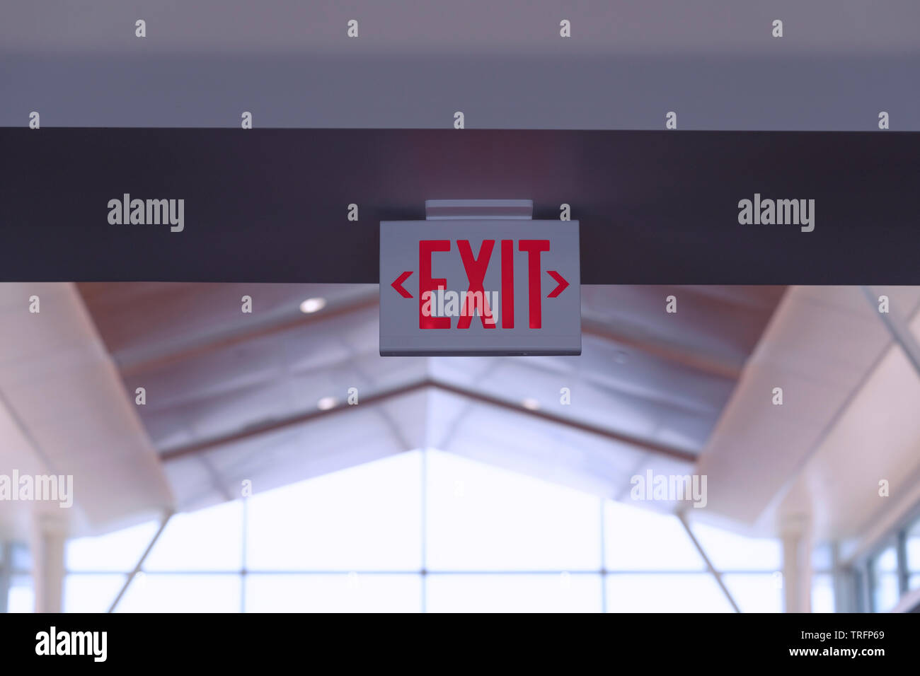 Exit Sign. Red Fire Escape Sign Hang on the Ceiling in the Airport. Stock Photo