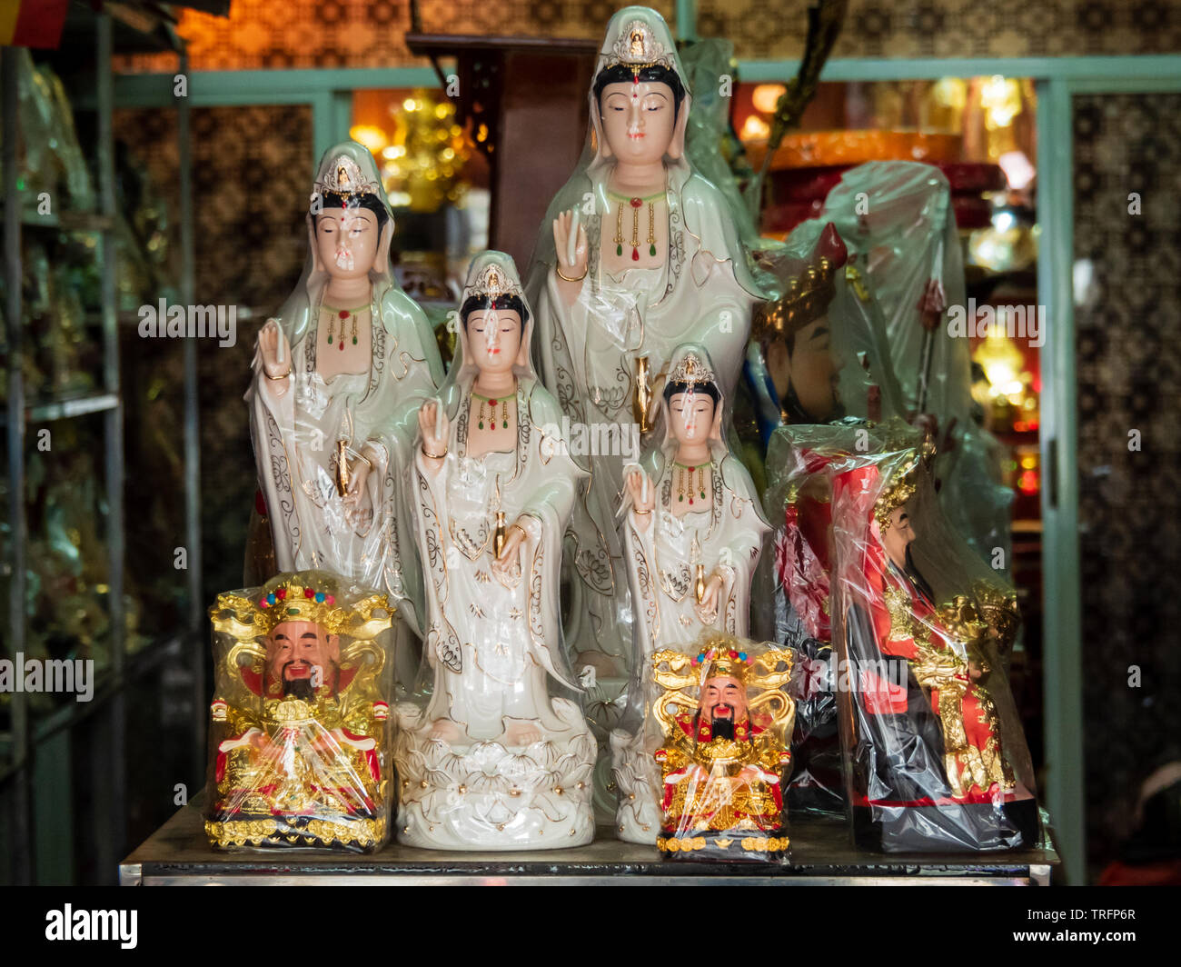 Figurines of the Goddess of Mercy, Kwan Yin / Kuan Yin and the God of Fortune, Cai Shen, at a Taoist / Daoist prayer items store Stock Photo