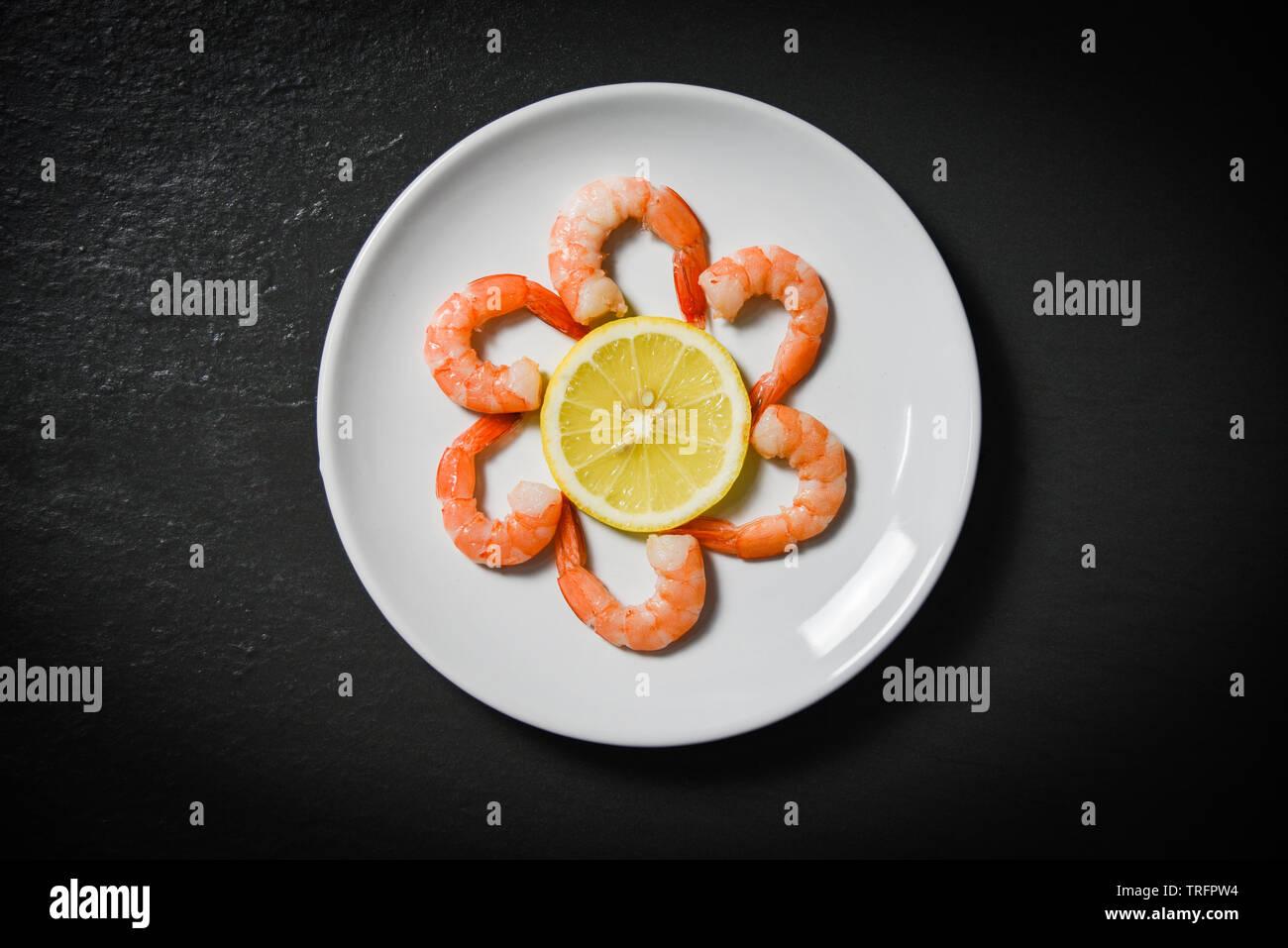 Shrimps prawns served decorate seafood plate and lemon on dark background Stock Photo