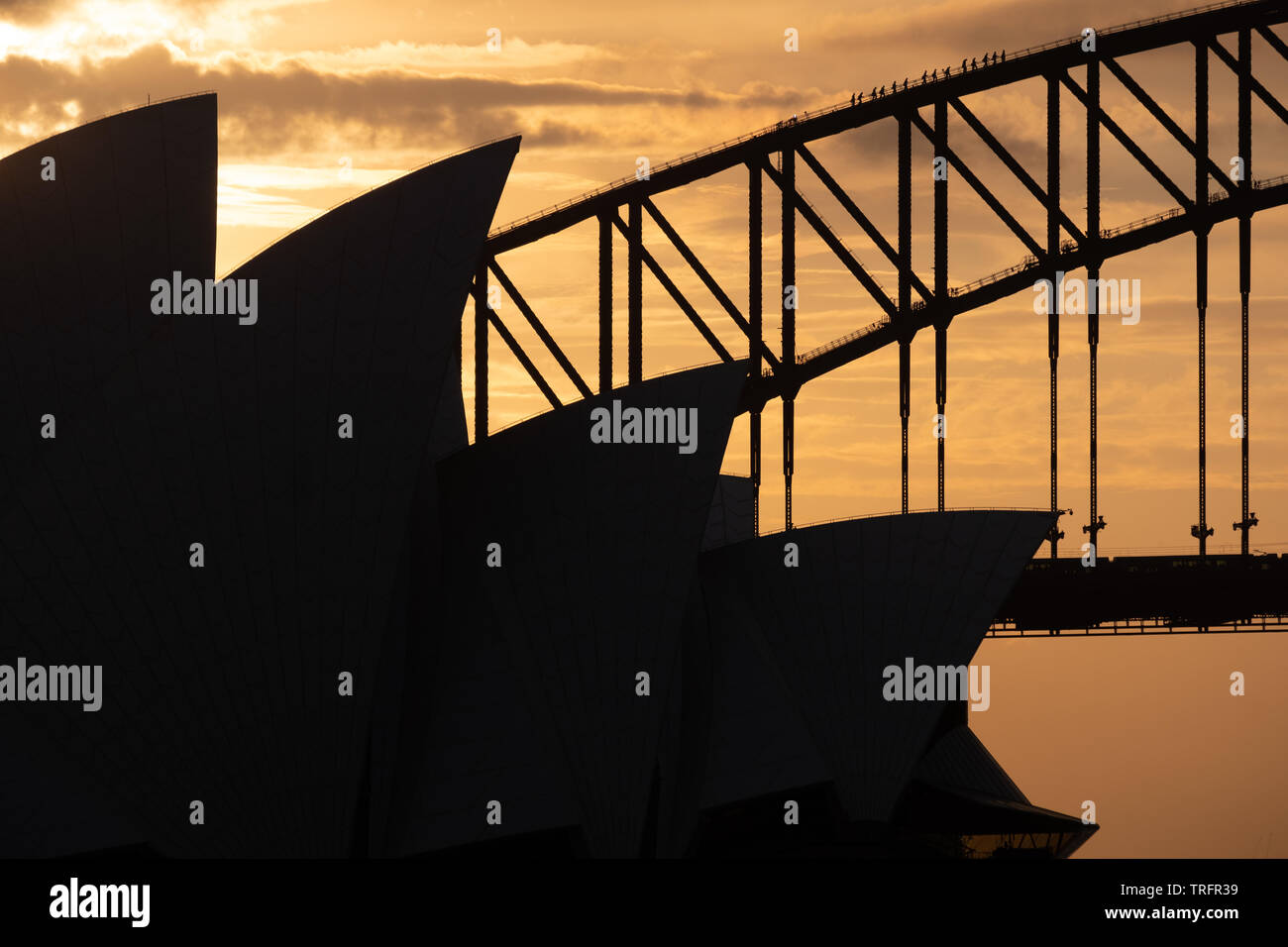 The Sydney Opera House and Harbour Bridge in silhouette with a orange evening sky. Bridge walkers can be seen climbing on the bridge. - Stock Image