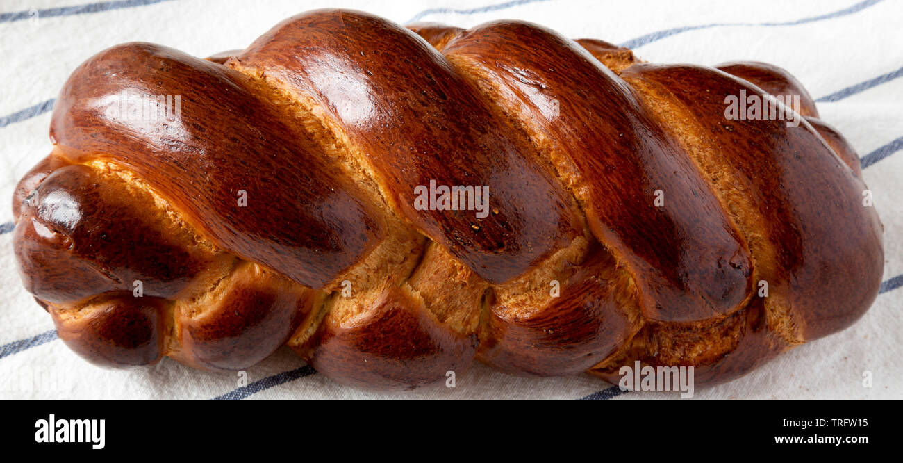 Home-baked jewish challah bread on cloth, side view. Closeup. - Stock Image