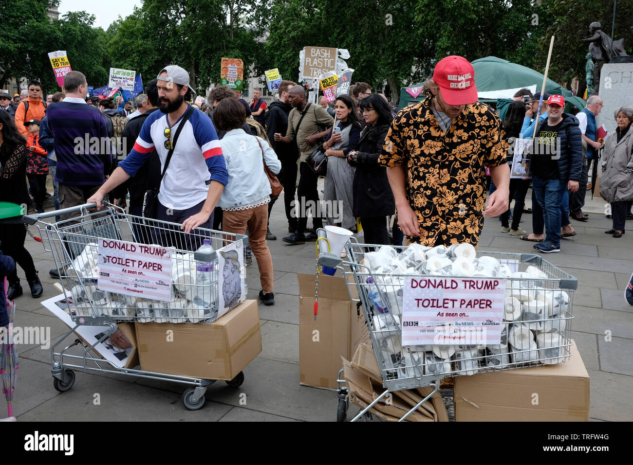 Two men selling Donald Trump toilet paper in Parliament Square, at a protest against the president of the Unted States, during his visit to UK. - Stock Image