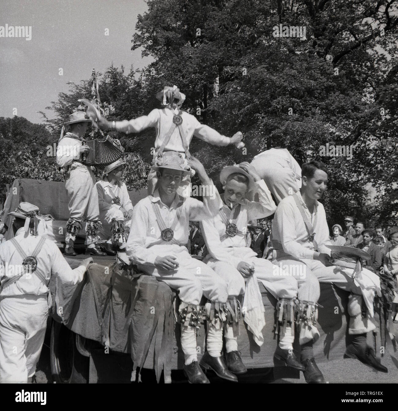 1950s, historical, On a hot summers day, a group of male morris dancers playing on a carnival float, with three of them taking a break from the dancing to enjoy a rest and a cigarette, England, UK. Morris dancing is a traditional English folk dance and an important part of summer fetes and carnivals, Stock Photo