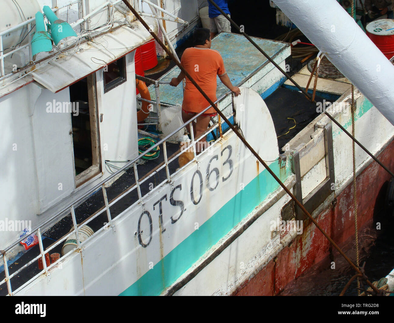Crewmen prepare a fish transhipment from an Asian-flagged tuna longliner into a carrier mothership. Stock Photo