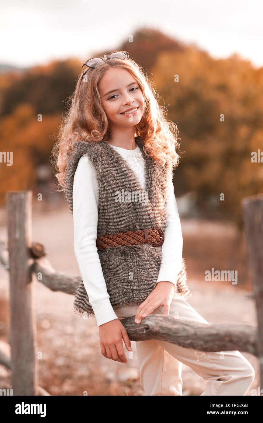 Beautiful blonde teenage girl 13-14 year old wearing fur vest, white knitted sweater and beige pants. Posing at country side. Looking at camera. Autum - Stock Image