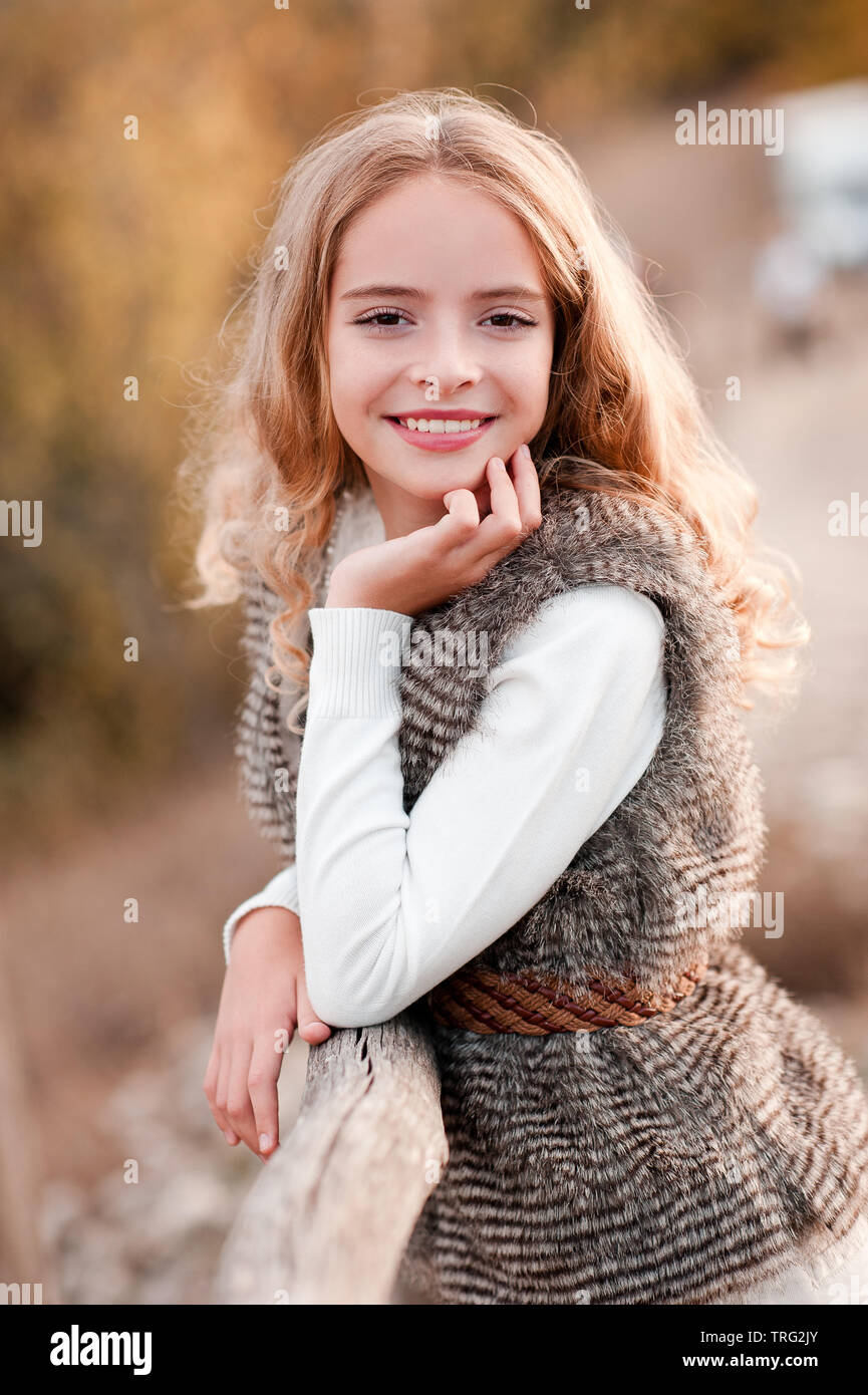 Smiling teen girl 12-14 year old wearing stylish fur vest and knitted sweater posing outdoors over nature background. Looking at camera. - Stock Image