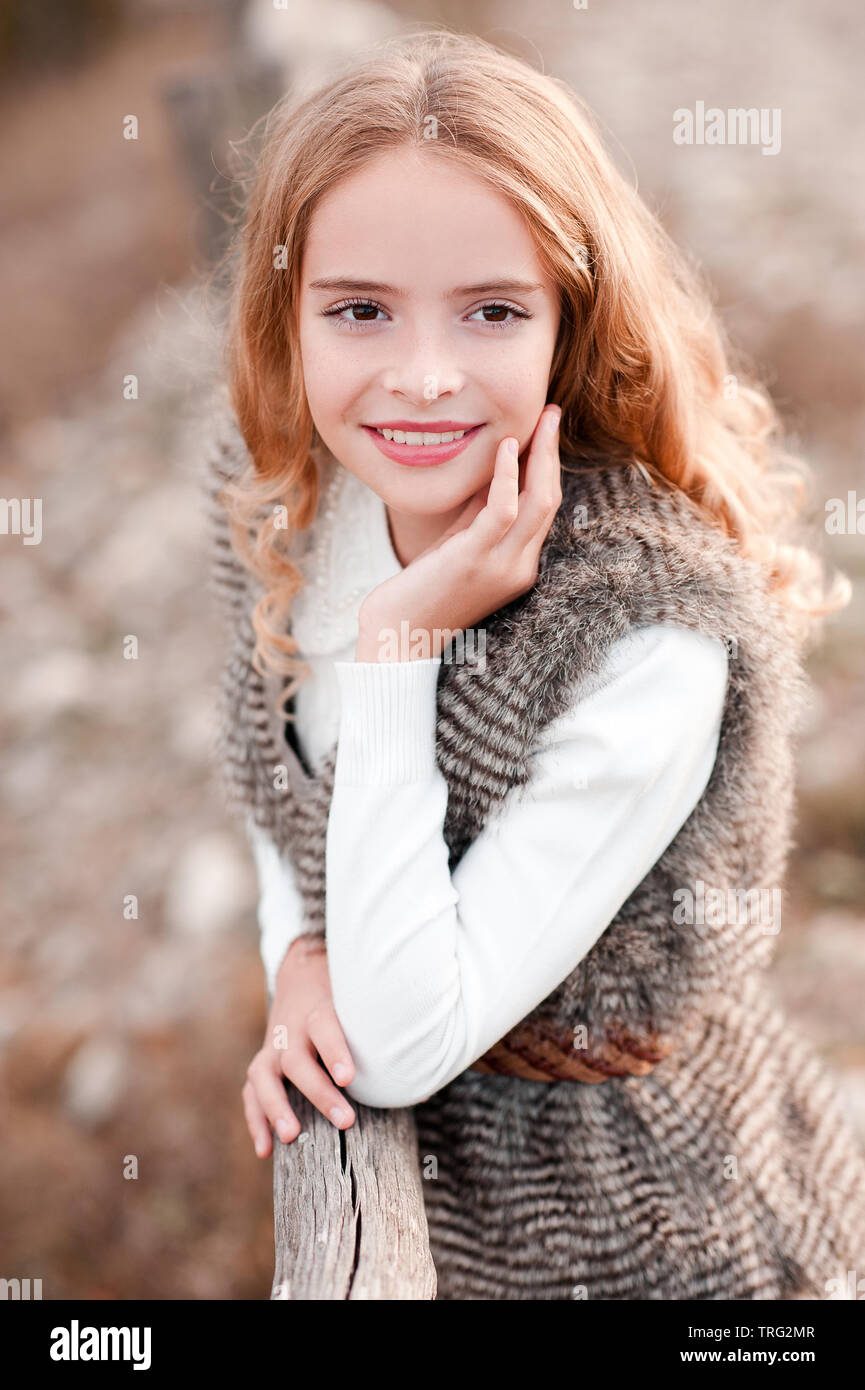 Smiling blonde kid girl 13-14 year old wearing fur vest and white sweater outdoors. Autumn season. Childhood. - Stock Image